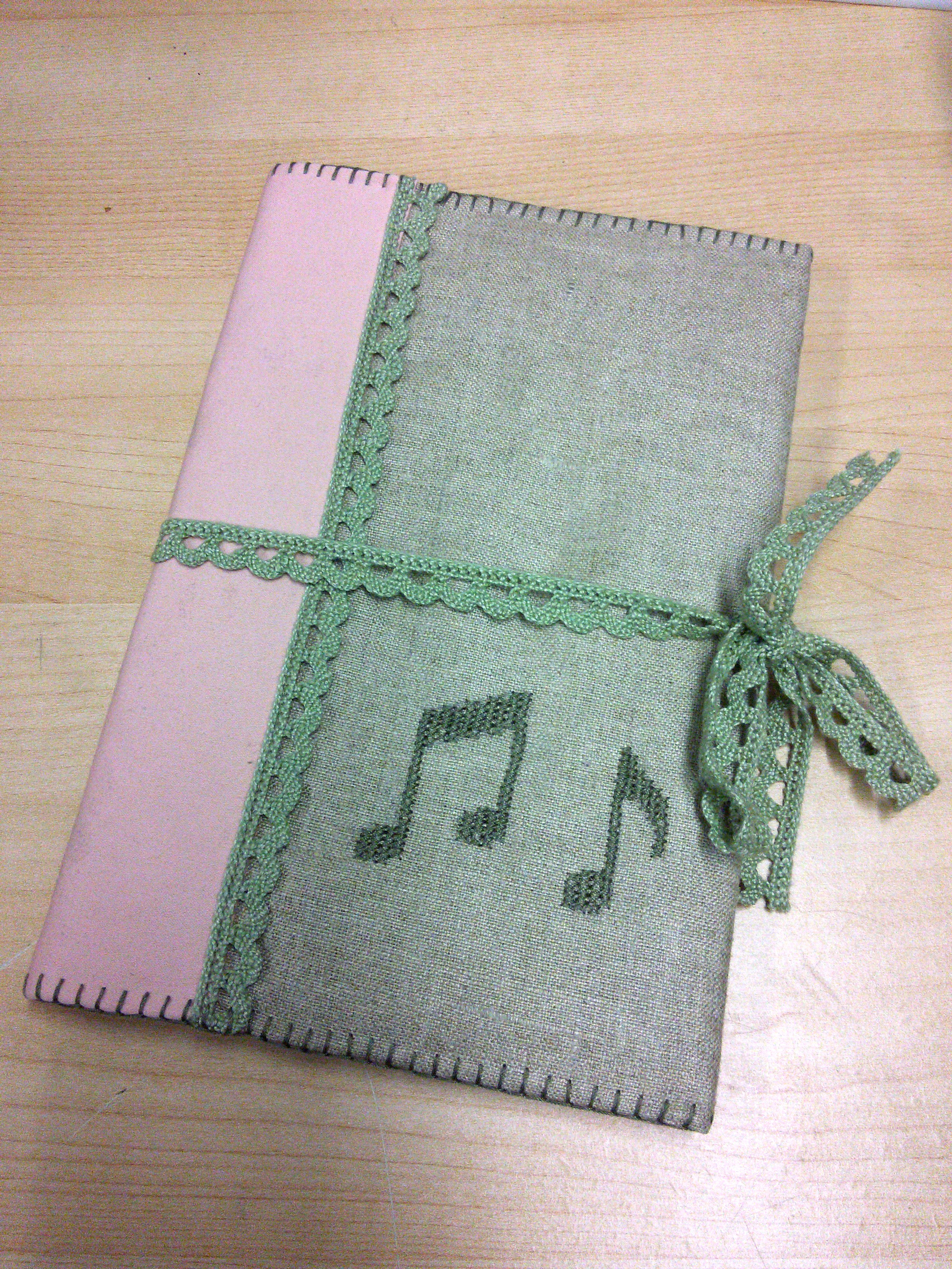 A photo of my songbook's cover, closed with a lacy ribbon tied around it.