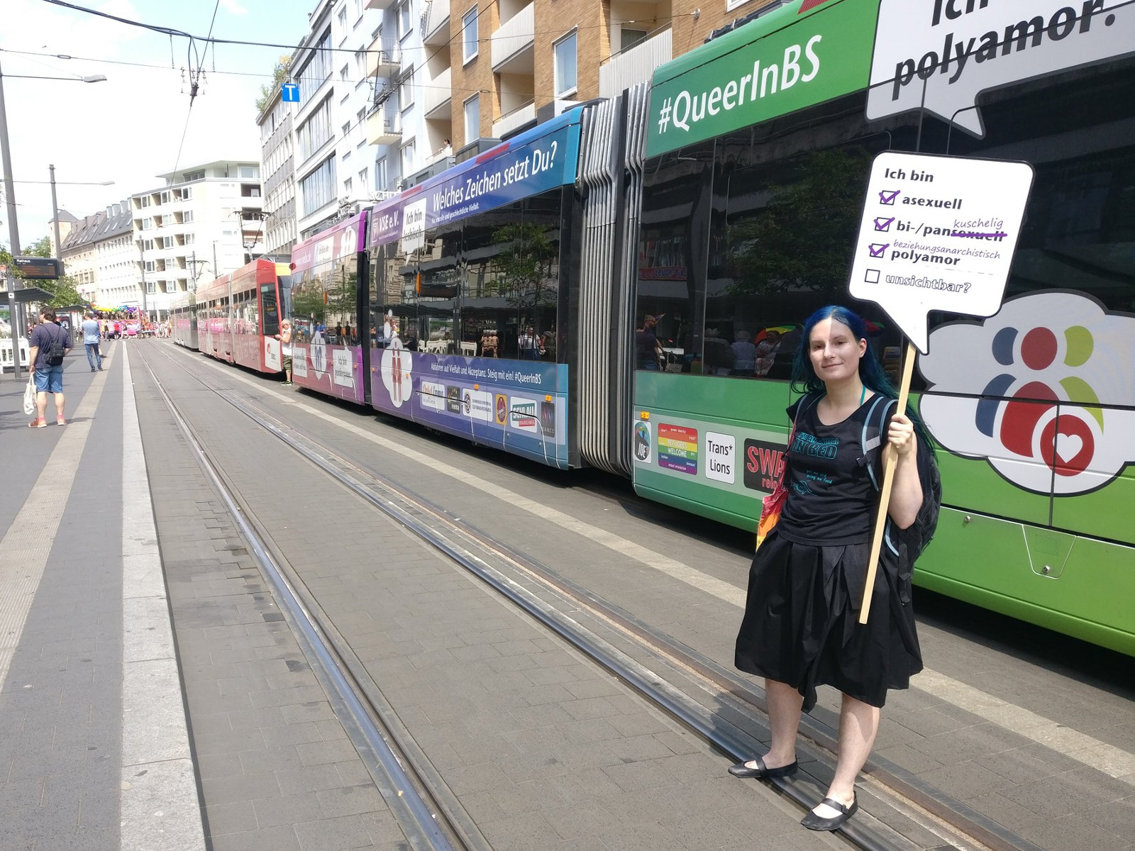 photo of me standing in front of the rainbow tram with my sign